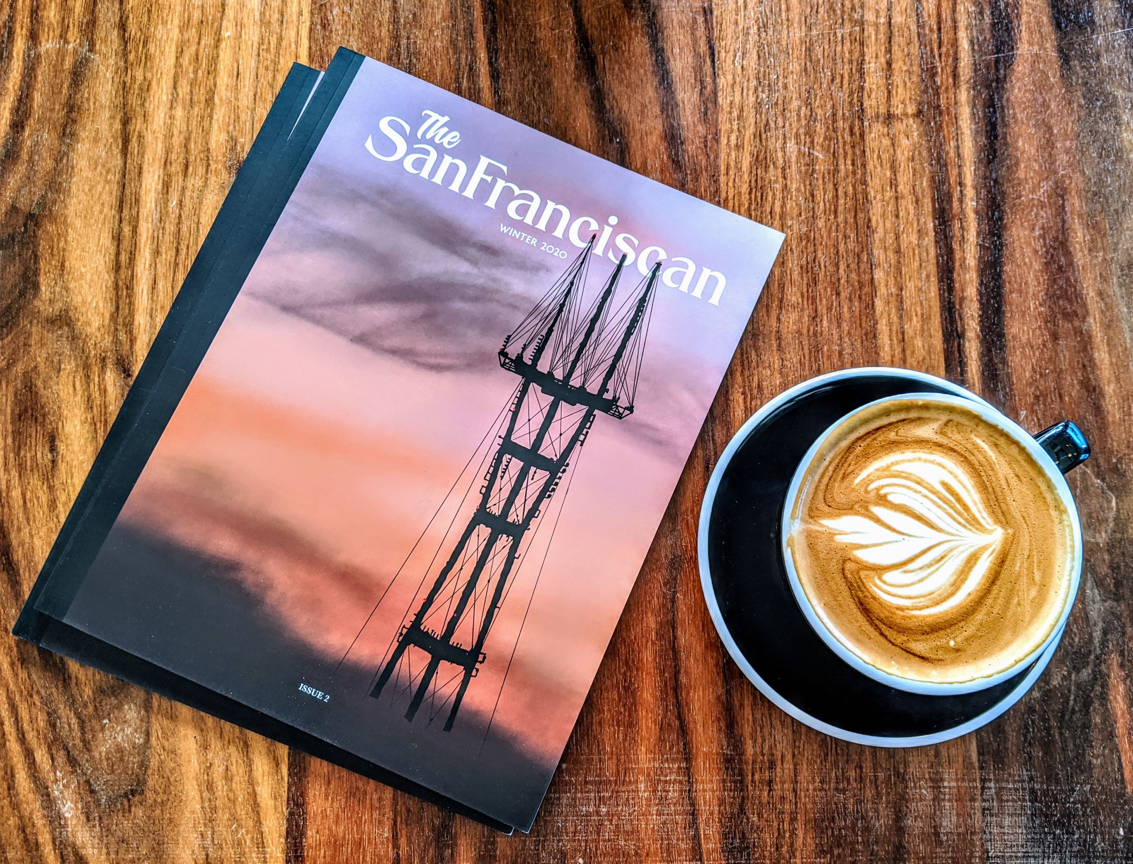 A copy of issue 2 next to some beautiful latte art on a wooden table